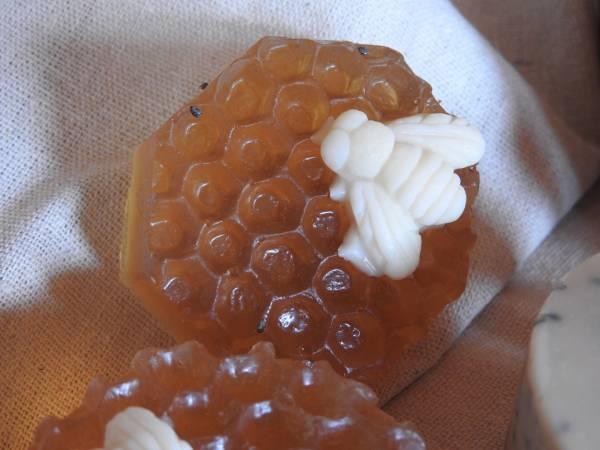 Jabon de miel con forma hexagonal con una abeja de color claaro